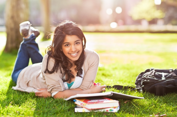 Student studying on university lawn